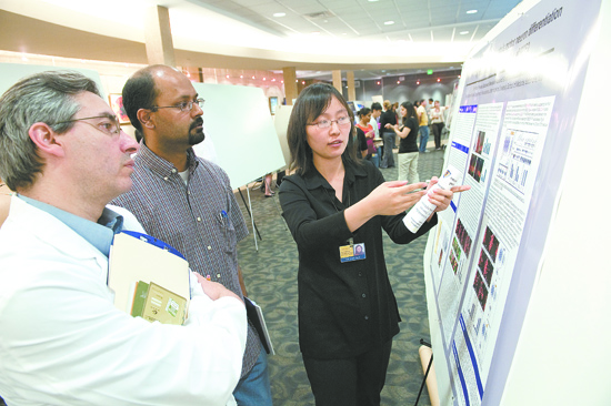 Ye Yan explains her research to faculty judges Angelo De Marzo and Vasan Yegnasubamanian, both of the Department of Oncology. Yan won first place in the basic translational poster category.