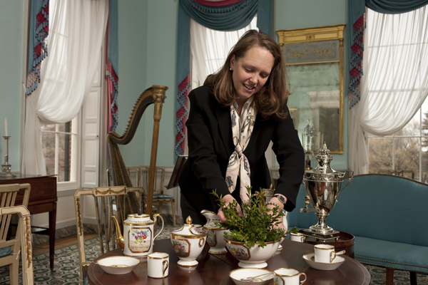 Catherine Rogers Arthur decorates a table in Homewood Museum's drawing room, one of the Carroll family's principal entertaining spaces. A hand-painted French porcelain coffee and chocolate service would likely have been used for holiday festivities. Photo: Will Kirk/Homewoodphoto.jhu.edu